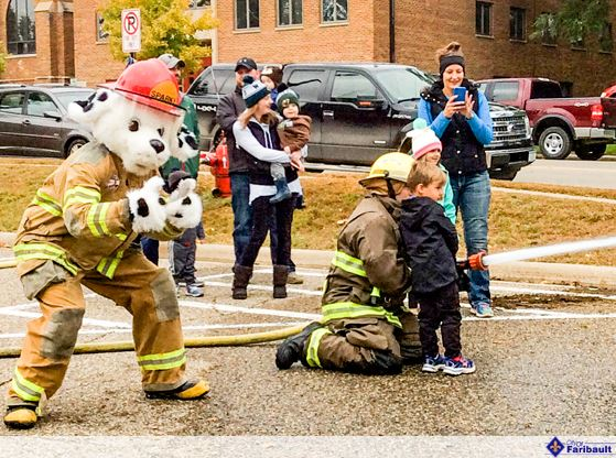 Image of a child spraying a fire hose at the Fire Deptartment Open House