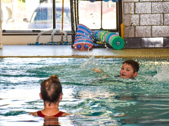 A young participant in the pool swimming during a private swim lesson.
