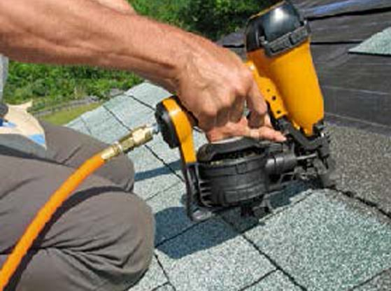 A picture of a man using a nail gun to put on shingles.
